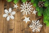 Beautiful paper snowflakes with fir branch on wooden background