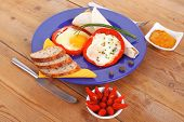 fried eggs and tortilla with salad , red hot pepper and mustard, served on blue plate with cutlery o