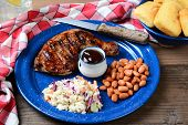 Closeup of a Barbecue chicken plate with cole slaw, pinto beans and corn bread. The meal is on a rustic wooden restaurant table with a red and white checked napkin and a glass of lemonade.