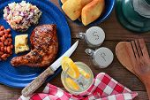 High angle shot of a barbecue chicken plate with cole slaw, pinto beans and corn bread. The meal is on a rustic wooden restaurant table with a red and white checked napkin and a glass of lemonade.