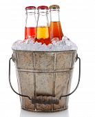 An old fashioned bucket filled with ice and soda bottles. Three different pop bottles are represente