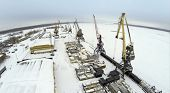 Aerial view to empty cargo dock with cranes and containers in the winter