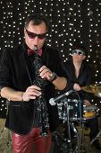 Saxophonist in a bow tie and sunglasses playing the saxophone with drummer in a club with garlands