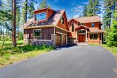 foto of red siding  - Big luxury house with brown and orange siding trim - JPG