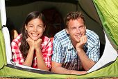 Happy romantic couple camping in tent looking in forest. Campers smiling happy outdoors in forest re