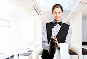 Waitress holding a bottle of champagne in a modern restaurant