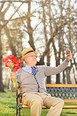 Elderly holding tulips and taking selfie outdoors