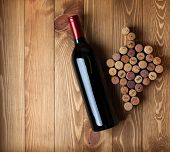 Red wine bottle and grape shaped corks on wooden table background with copy space