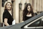Two young fashion women on the car parking