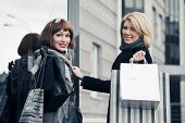 Two fashion young women with shopping bags