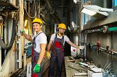 Two worker in a safety hats  on a factory near near machine