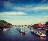 Vintage retro hipster style travel image of turist boats on Vltava river in Prague, Czech Republic w