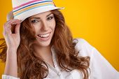 Young Woman with spring hat against yellow background