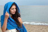 Beautiful young woman with long black hair wrapped in a blue scarf