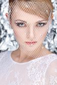 Beautiful white-headed girl in a veil on a silvery background, emotions, cosmetics