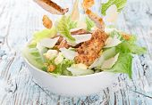 foto of caesar salad  - Caesar salad with chicken and greens on wooden table - JPG