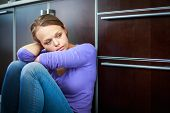 Depressed young woman, sitting on the kitchen floor, feeling down