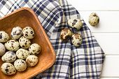 Quail eggs in wooden bowl on kitchen table