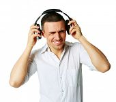 A man not enjoying what he is hearing, listening to music over white background