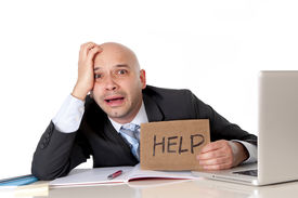 stock photo of bald head  - overworked unhappy bald business man in stress wearing suit holding help sign working on computer - JPG