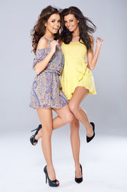 picture of vivacious  - Two vivacious beautiful young women in trendy short summer dresses posing arm in arm balanced on one foot smiling at the camera - JPG