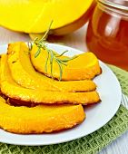 Pumpkin baked with honey in bowl on board