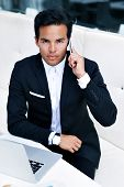 Young handsome man in a suit sitting in cafe talking on the phone,