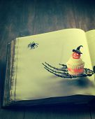 Cupcake for Halloween sitting on the hand of a skeleton against the pages of a book