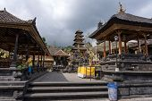 BALI, INDONESIA - SEPTEMBER 20, 2014: A lady prays at a family temple inside the Besakih Temple Complex. It is the largest and most important Hindu temple on Bali Island.