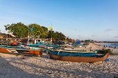 BALI, INDONESIA - SEPTEMBER 20, 2014: Fishing boats fill the beaches of the Jimbaran fishing village. A typhoon storm in the ocean prevented the fishermen from going out to sea the day before.