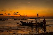 BALI, INDONESIA - SEPTEMBER 20, 2014: A group of fishermen prepares their boat to go out to sea at dusk. The fishery industry is an important economic activity on Bali Island.