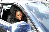 stock photo of encounter  - Young attractive African woman driving her car grimacing as she encounters a hold up in the traffic viewed through the open side window - JPG