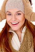 Vivacious gorgeous young woman in winter fashion laughing as she holds her gloved hands to her knitt
