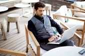 Confident and serious businessman working with computer pc in beautiful restaurant