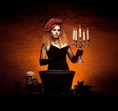 foto of dungeon  - Young and beautiful witch indulging in witchcraft in a dungeon - JPG