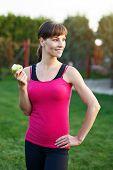 Brunette Woman In Sportswear Holding Apple