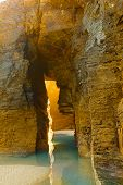 Stone arch on Playa de Las Catedrales on a sunset