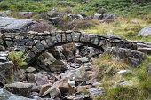Old Ancient Packhorse Bridge Over Mountain Stream In Autumn