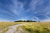 image of wispy  - Wispy clouds over a Gravel track leading to Badbury Rings Iron age fort - JPG