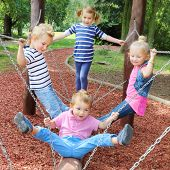 Hilarious kids have a fun on a garden swing.