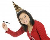 A pretty young teen in a party hat celebrating the New Year.  She's twirling a noisemaker.  On a white background.