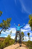 Hiking man reaching summit top cheering celebrating on mountain top with arms up outstretched towards the sky. Happy male hiker.