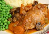 Casseroled chicken breast served with mashed potato and peas.