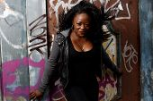 Smiling Black Woman Posing At Wall With Vandals