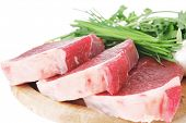 butchery : fresh raw beef lamb fillet ready to cooking with green stuff on wooden plate isolated ove