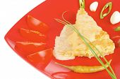 food : vegetable casserole piece over red plate ready to eat with chives tomatoes peppers and chives isolated over white