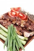 fresh grilled meat beef ribs with asparagus thyme and tomatoes on wooden plate isolated over white b