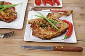 meat : chicken quarters garnished with green sweet peas and and cutlery on white plates over wooden