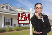 Attractive Mixed Race Woman in Front of House and For Sale Real Estate Sign.