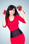 Beauty portrait of gorgeous attractive young girl like santa in red costume with alluring christmas vivid presents hanging and sexy thin waist with black belt in new year eve isolated over studio room